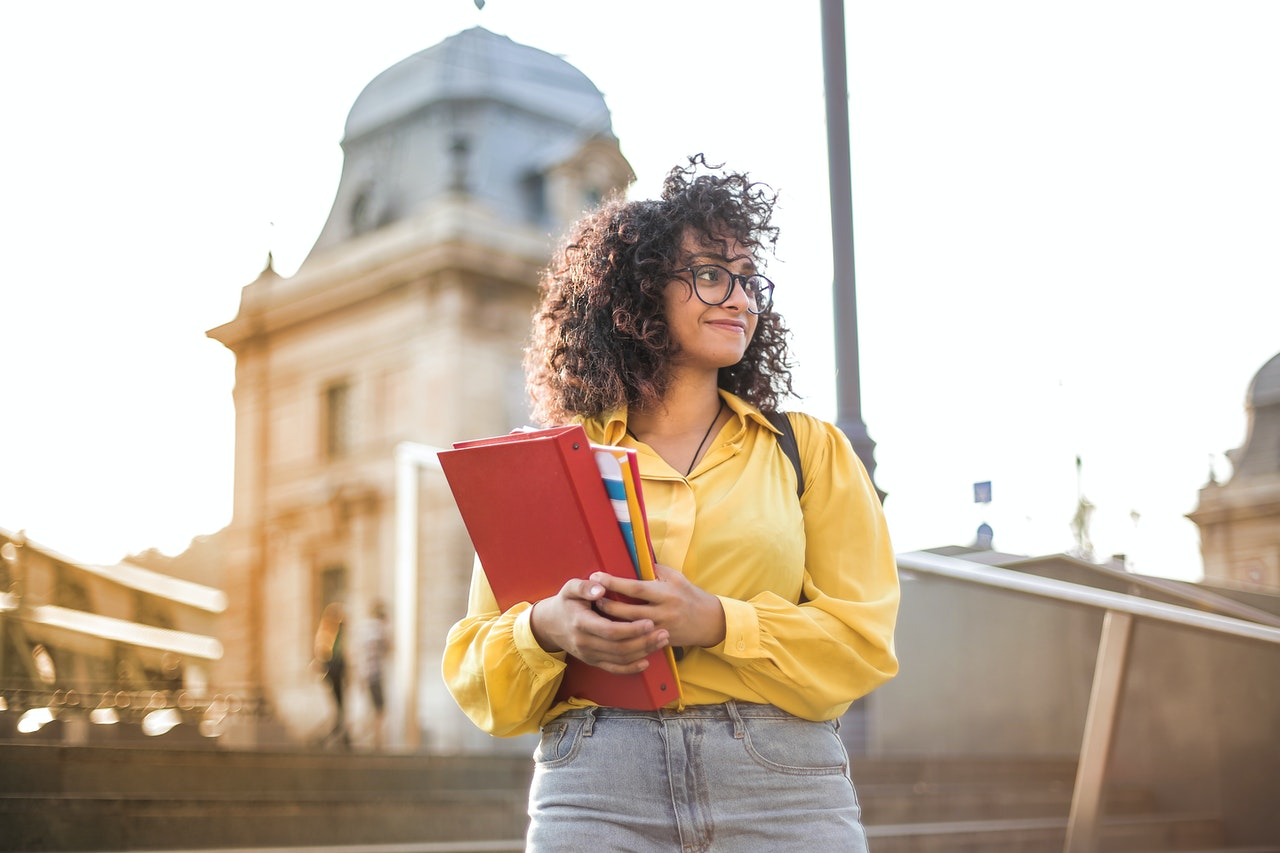 young woman holding binder and books